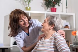 female caretaker helping senior woman in private duty home care